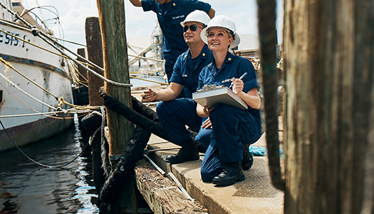 Two Coast Guard members at a dock taking notes