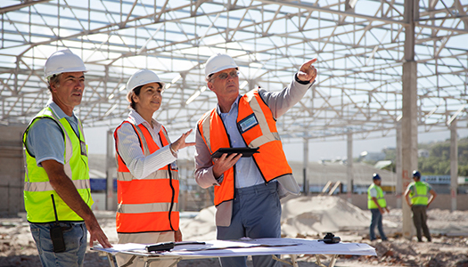 Three construction workers engaging in a discussion at a construction site