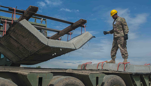 A Military service member standing atop a flatbed trailer at a construftion site