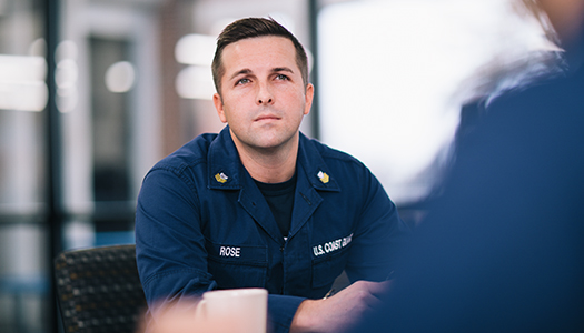 A US Coast Guard member sitting in a room with his colleague