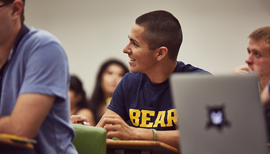 A student smiles while sitting in a classroom