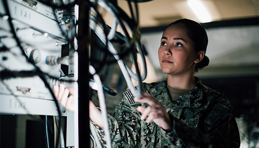 A US Navy service members examines a series of cables behind computer servers.