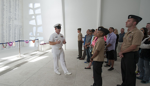 A Navy service member with a large group gathered inside a memorial area