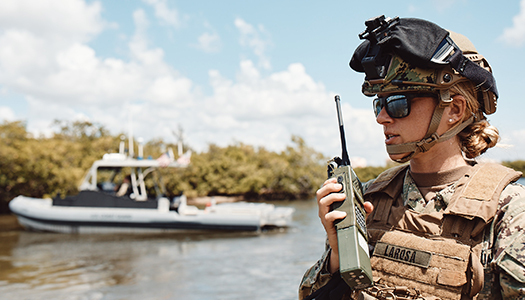 A US Navy service member standing in a boat communicating on a radio