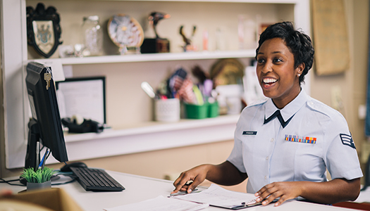 An Air Force service member sitting on her desk and handling paperwork